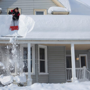 Roofing contractor removing thick snow from a roof.