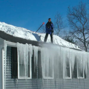 Roofing contractor removing ice from a roof.
