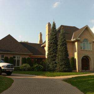 Large brick house with a finished shingle roof.