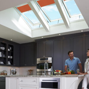 Couple in a kitchen under large skylights.