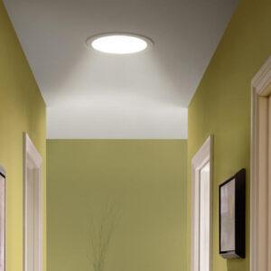 Small circular skylight in hallway ceiling.