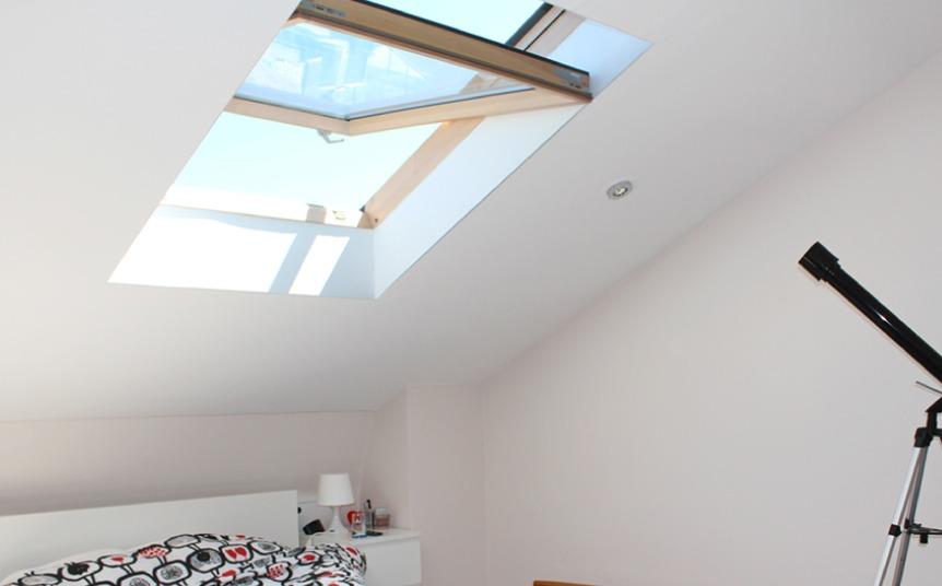 Open skylight in a white bedroom.
