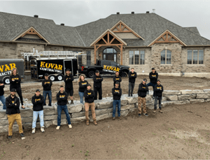 kovar roofing team posing in front of a large mansion