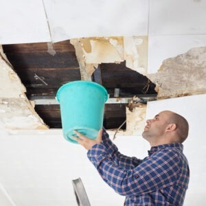 man catches water leaking roof