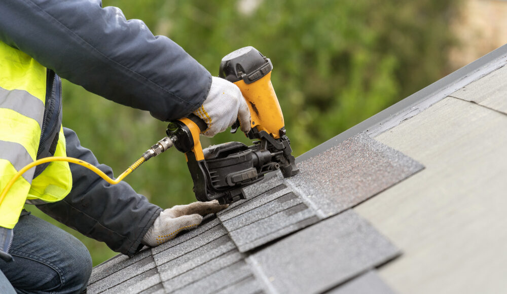 roofing contractor installs shingles