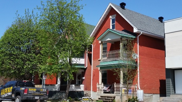 Red painted brick house with light grey shingles by Kovar Roofing