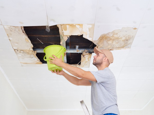 a man holding a bucket under a leaking roof